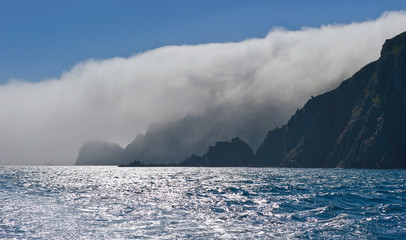 High, steep coast, covered in mist.