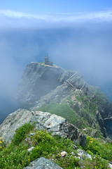The ruins of lighthouse, on the high banks covered with fog.
