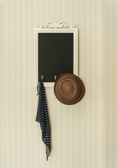 Vintage slate chalk board with handkerchief and brown hat on the