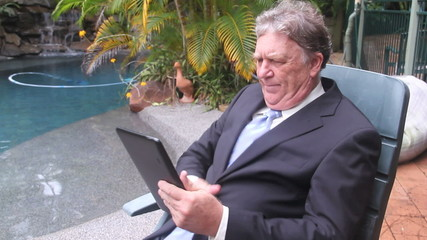 Businessman in chair using tablet by swimming pool.