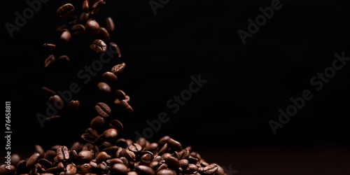 High contrast image of coffee beans being dropped onto pile with - 76458811