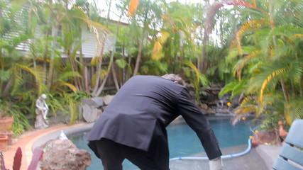 Businessman walking around swimming pool then sitting down