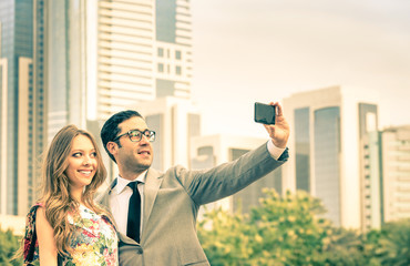 Hipster couple taking a selfie at business center outdoors