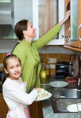 Daughter and mother washing dishes