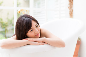 young asian woman relaxing in the bathtub