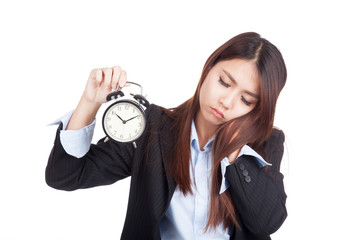 Young Asian businesswoman sleepy with alarm clock