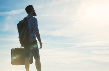 Bearded hipster traveler looking at sun