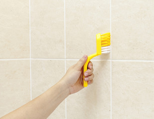 woman using brush to wash shower tiles