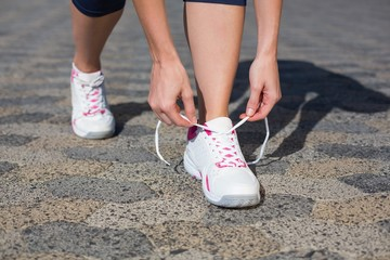 Woman tying her shoelace on running shoe