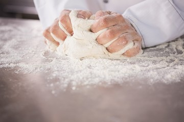 Close up of baker kneading dough on counter