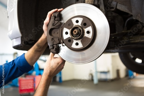 canvas print picture Focused mechanic adjusting the wheel
