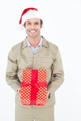 Happy delivery man wearing Santa hat while holding gift