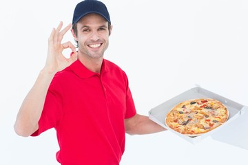 Delivery man gesturing okay while holding fresh pizza