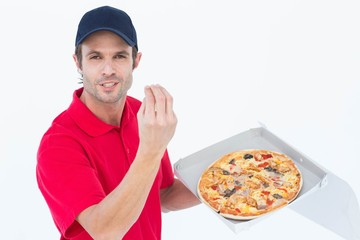 Delivery man gesturing while holding fresh pizza