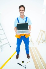 Portrait of repairman holding laptop