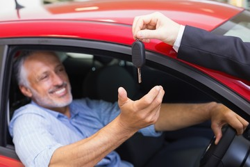 Smiling man driving a car while salesman his giving key