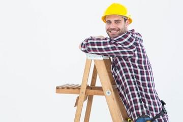 Smiling repairman climbing ladder