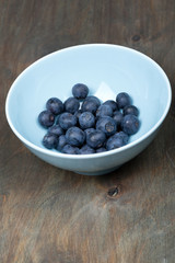 blueberries in a bowl on a wooden table, vertical