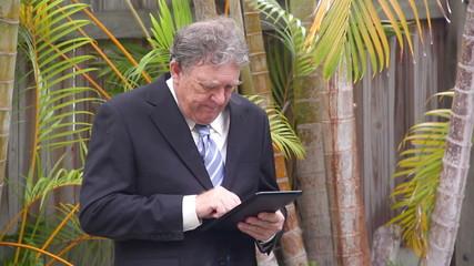 Businessman walking around pool working on tablet.