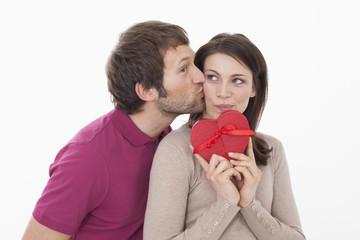 Frau mit herzförmiger Geschenk-Box, Mann küsst sie