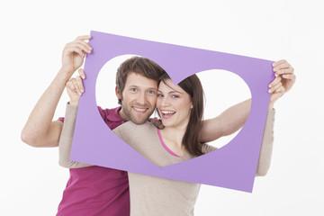 Paar sieht durch herzförmigen Rahmen