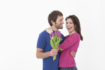 Frau mit Blumen und umarmt Mann