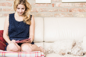 Happy blonde sitting on her sofa using tablet at home