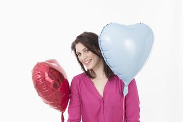 Junge Frau mit herzförmigen Luftballons, Portrait