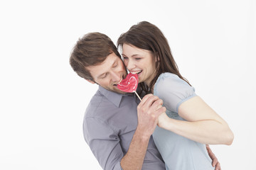 Paar isst herzförmige Lutscher, Lächeln