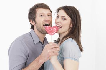 Paar isst herzförmige Lutscher, Portrait
