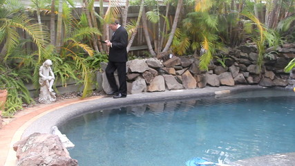 Businessman walking around pool working on tablet.