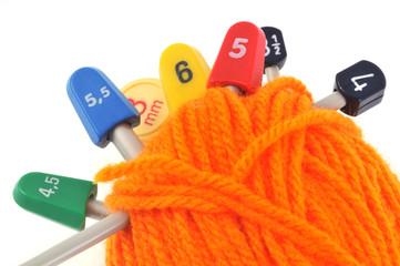 Aiguilles à tricoter plantées dans une pelote de laine