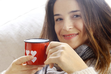 smiling girl  drinking something from Valentine heart painted gl