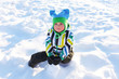little child sitting on the snow in winter outdoors
