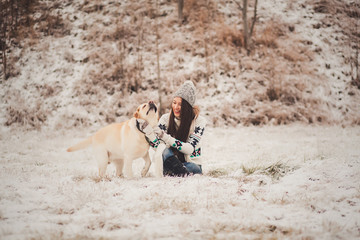 happy girl in sweater playing with dog in winter park