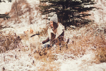 Cute girl sitting with dog in winter park