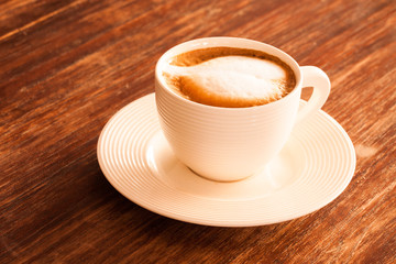 A cup of hot latte  coffee  on a wooden table.