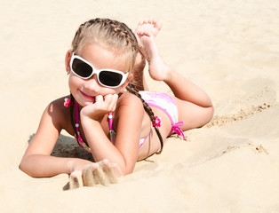 Happy cute little girl in sunglasses lying on the sand