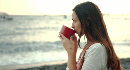 Beautiful Young Woman Drinking Coffee At The Beach Sunrise