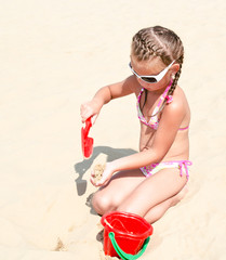 Cute smiling little girl playing on beach