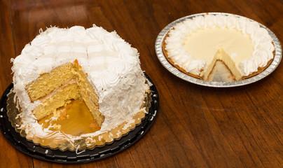 Cut Coconut Cake and Lemon Meringue Pie on Wood Table