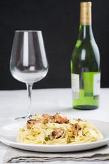 Tallarines con salmón y vino blanco en la mesa del restaurante