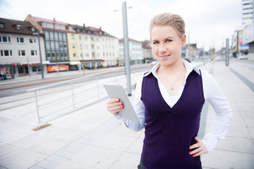 young business woman holding her tablet in public