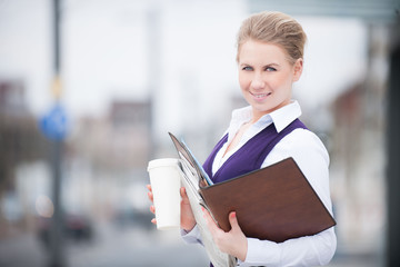 young business woman with coffee and documents in public