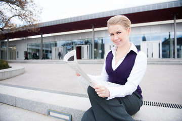 young business woman reading the news in public