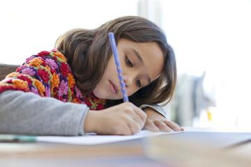 Niña concentrada escribiendo
