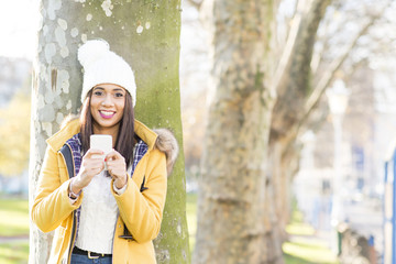 Happiness beautiful latin woman with cap holding phone, outdoor.