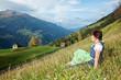 Woman in dirndl sitting on mountain meadow
