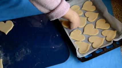 Woman Puts Heart Shaped Dough On A Baking Sheet