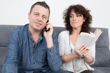 homme au téléphone et femme en train de lire